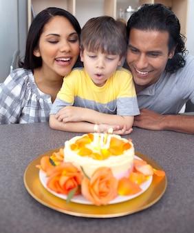 彼の誕生日の蝋燭を吹く愛らしい小さな男の子