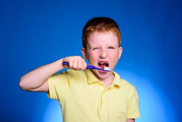 歯ブラシを持ってカメラに微笑んでいる愛らしい男の子。モックアップ、無料のspase。歯ブラシでかわいい面白い男の子。歯科の概念-彼女の歯を磨く空白の白いシャツを着た笑顔の10代の少女。