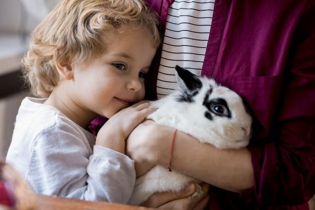 Очаровательный маленький мальчик обнимает кролика
