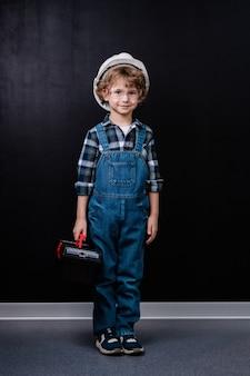 黒いスペースに立っている間、ヘルメット、デニムのオーバーオール、ツールボックスを保持している眼鏡の愛らしい小さな男の子