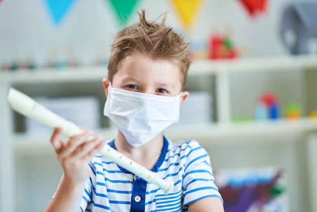 코로나 바이러스 전염병으로 인해 마스크가 달린 유치원에서 사랑스러운 어린 소년