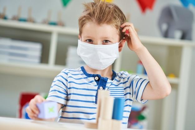 コロナウイルスのパンデミックのためにマスクをつけた幼稚園の愛らしい少年