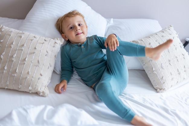 Очаровательный маленький мальчик лежит и играет в своей постели дома. раннее утро. ребенок просыпается утром с улыбкой.