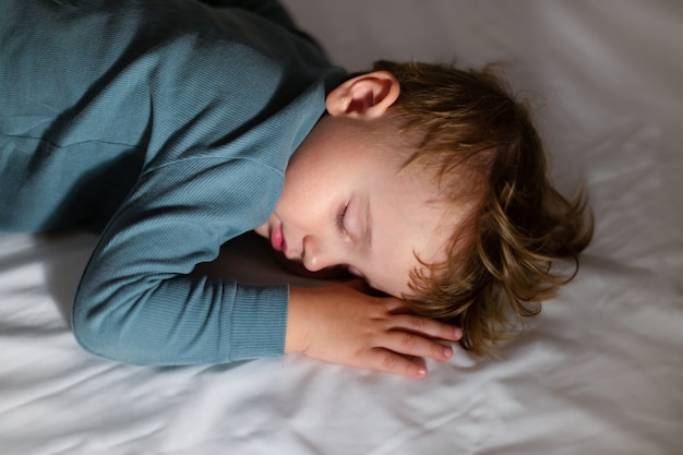 Adorable little boy is sleeping in his bed in the dark at home. bedtime. child resting and dreaming at night.