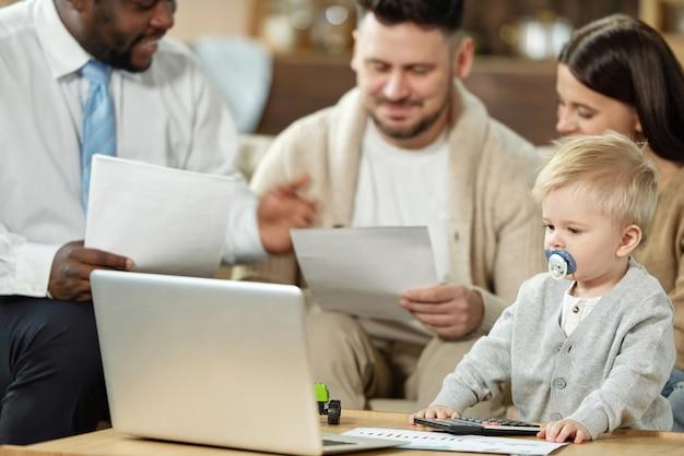 부모가 주택 융자에 대한 민족 컨설턴트와 토론하는 동안 사랑스러운 어린 소년 노트북을 찾고