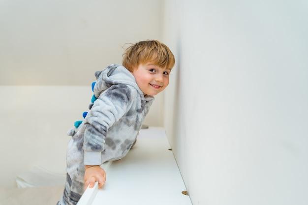 Очаровательный маленький мальчик трех лет, играющий в постели у себя дома