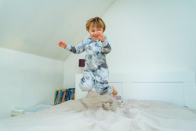 Очаровательный маленький мальчик трех лет играет в спальне дома