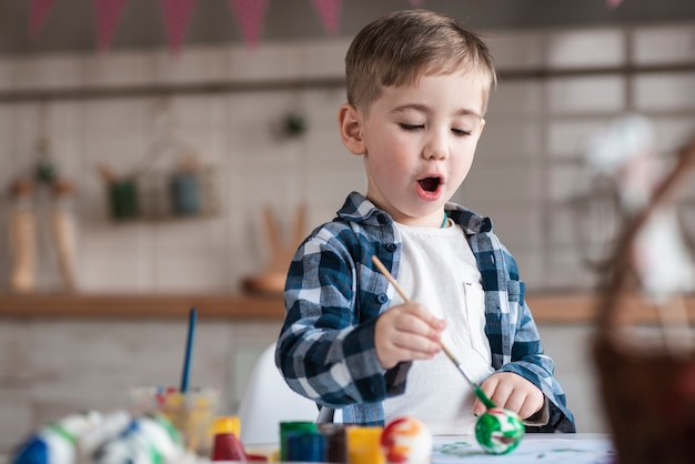 Adorable little boy painting easter eggs