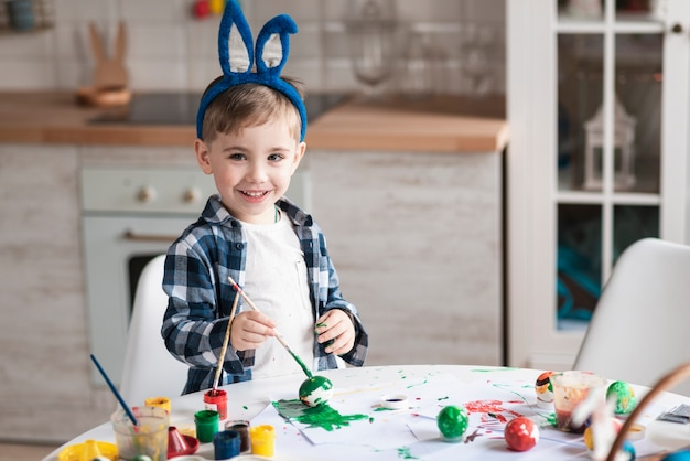 Adorable little boy painting eggs for easter
