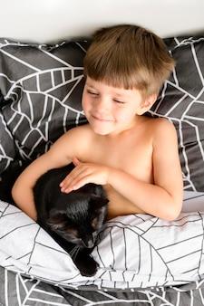 Прелестный маленький мальчик гладит свою кошку