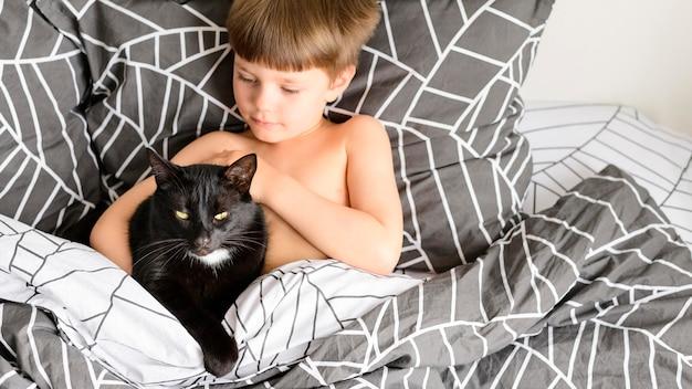 Прелестный маленький мальчик гладит своего котенка