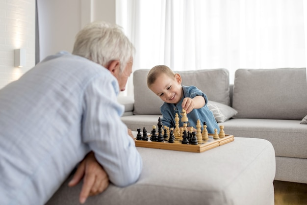 Adorable little boy playing chess with his grandfather