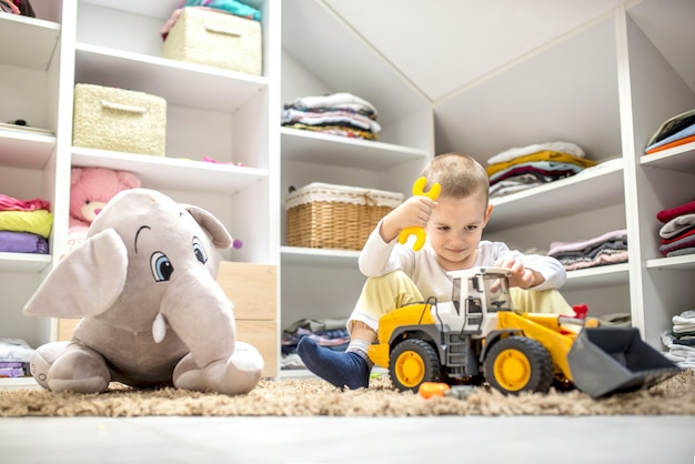 Adorable little boy playing with toys while sitting on the floor in his playroom