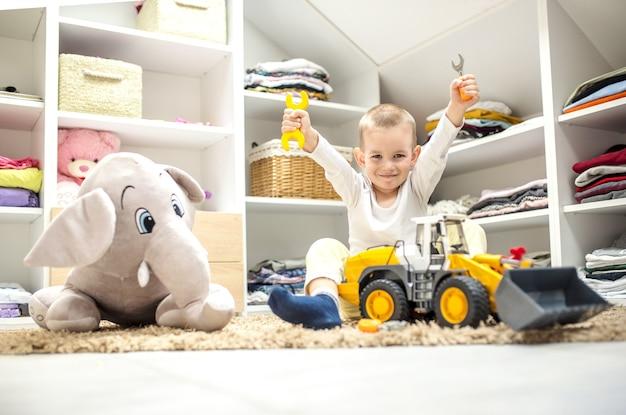 그의 놀이방에서 바닥에 앉아있는 동안 장난감을 가지고 노는 사랑스러운 작은 소년