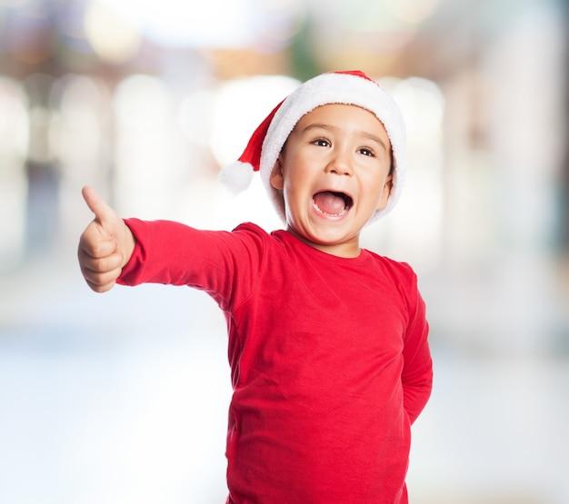 Adorable little boy showing a positive sign