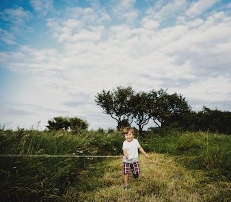 Adorable little boy stands on a green field in the rays of evening