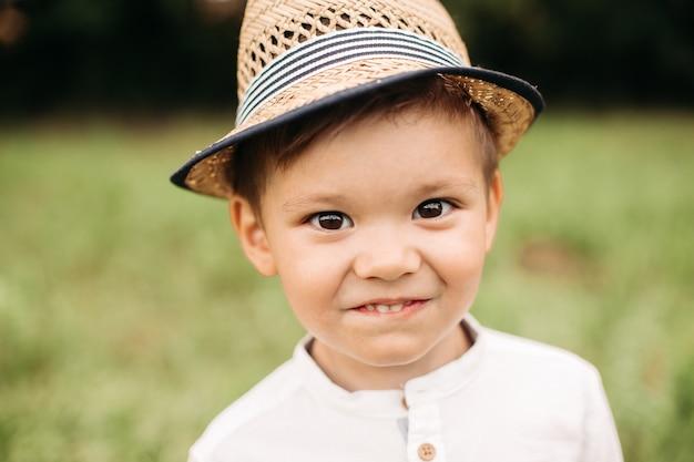 Adorabile ragazzino in cappello estivo. colpo in testa di un simpatico ragazzino in età prescolare con cappello estivo che sorride felicemente alla telecamera sullo sfondo del parco sfocato.