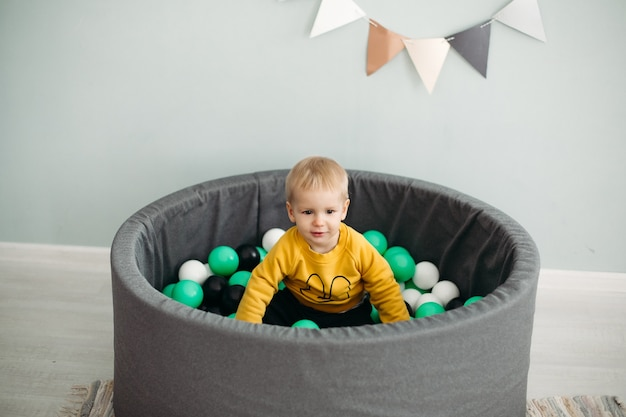 Adorable little boy with blonde hair sitting in ball pool with different green, white and grey plastic balls