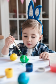 Adorable little boy with bunny ears painting eggs for easter