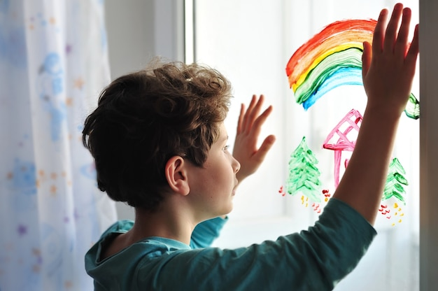 A adorable little boy with curly hair stands at a painted window with his hands up