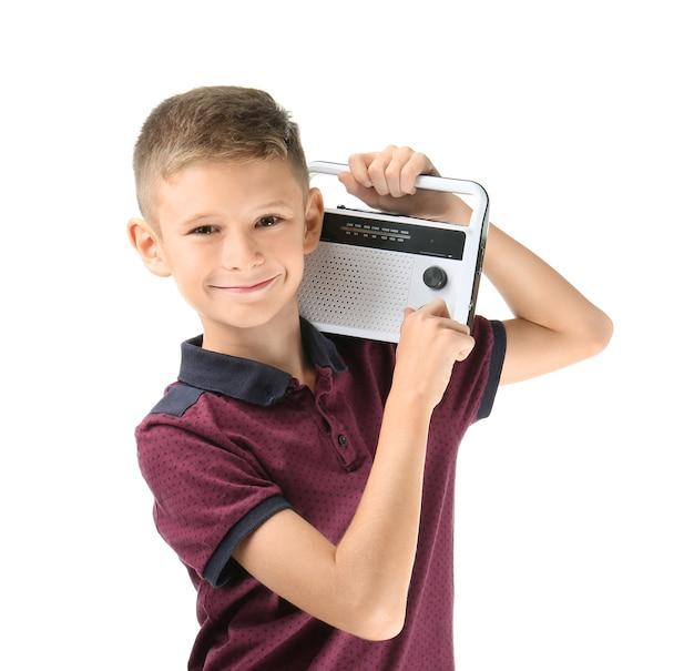 白い表面にラジオを持った愛らしい小さな男の子