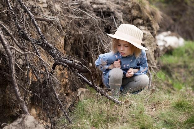 5歳の愛らしい小さな白人の女の子は、森の中で上向きの根を持つ倒れた木の隣に座っています