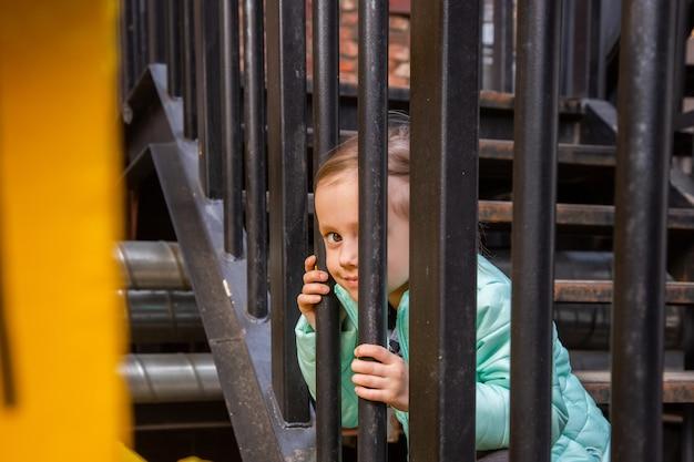 愛らしい白人の女の子が通りすがりの人を見て興味を持って鉄の階段に座っています