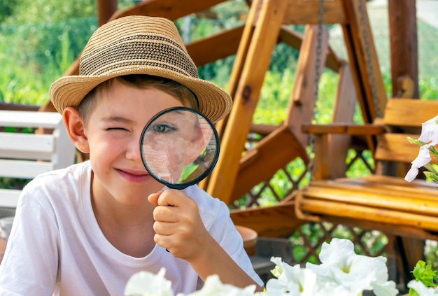 Adorable little child boy in straw hat look at green plant leaves and flowers with magnifying glass. kid observing, exploring nature and environment. early development and skills. young naturalist,
