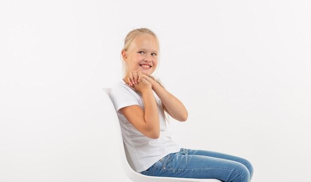 白い背景の上の椅子に座っている長いブロンドの髪を持つ愛らしい小さな子供の女の子。