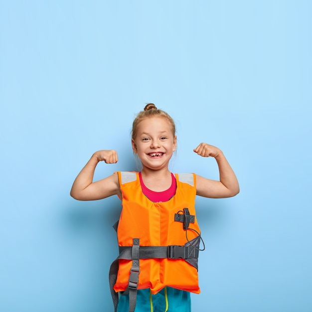 Adorable little child raises arms and shows muscles, wears orange inflated lifejacket