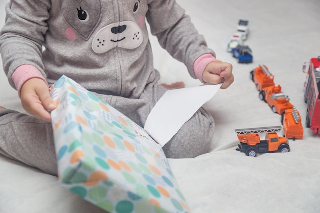 Очаровательный маленький ребенок распаковывает подарки, сидя на кровати