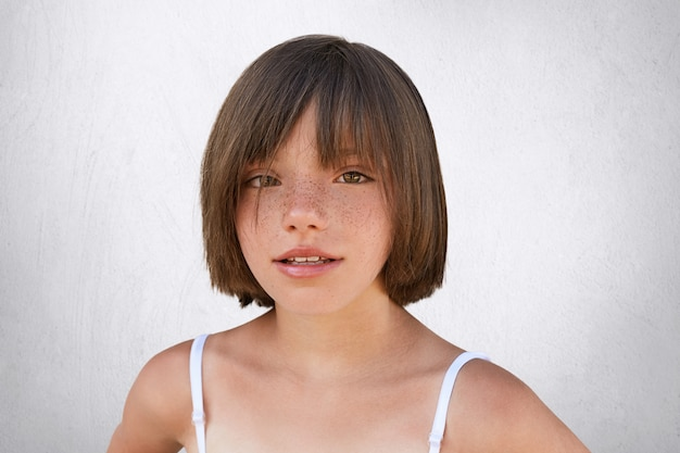 茶色の魅力的な目、そばかすのある肌、スタイリッシュな髪型の薄い唇、夏の服を着て、白でポーズをしながらカメラを直接見ている愛らしい小さな子供。