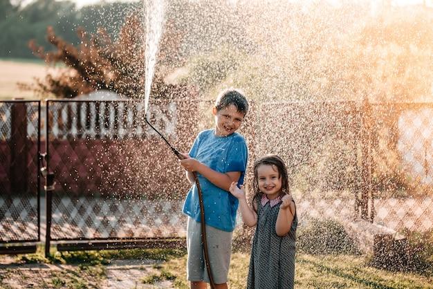 日没の暑くて晴れた夏の日に庭のホースと一緒に遊んでいる愛らしい小さな子供たち