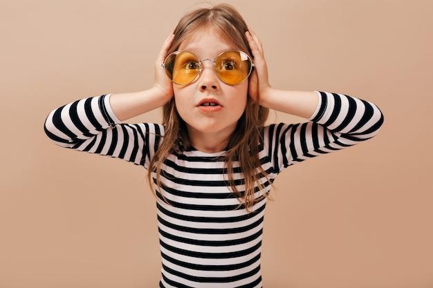 둥근 노란색 안경을 쓰고 사랑스러운 작은 귀여운 소녀는 걱정, 머리에 손을 잡고 멀리보고 보인다.