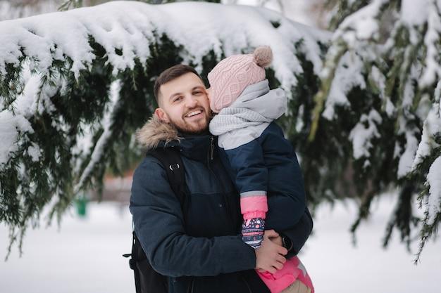 Очаровательная маленькая дочка со своим прекрасным папой у большого заснеженного дерева