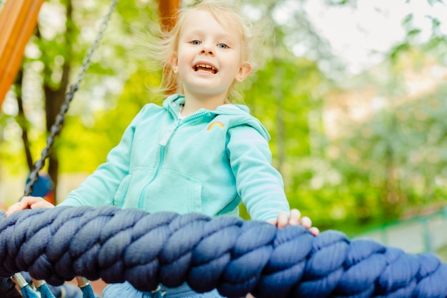 Adorable little girl 4 years old having fun on a round rope swing in a playground in the summer day.