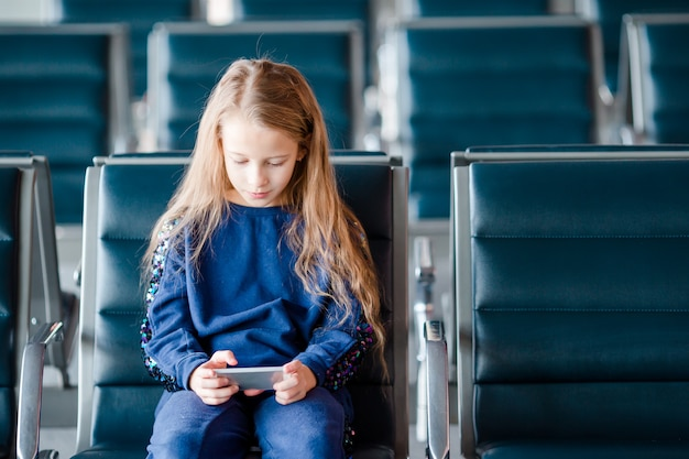 Adorable little girl in airport near big window indoor