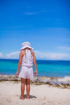 Одна прелестная маленькая девочка смотрит на море на белом пляже