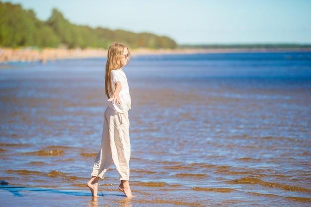 Прелестная маленькая девочка на пляже во время летних каникул