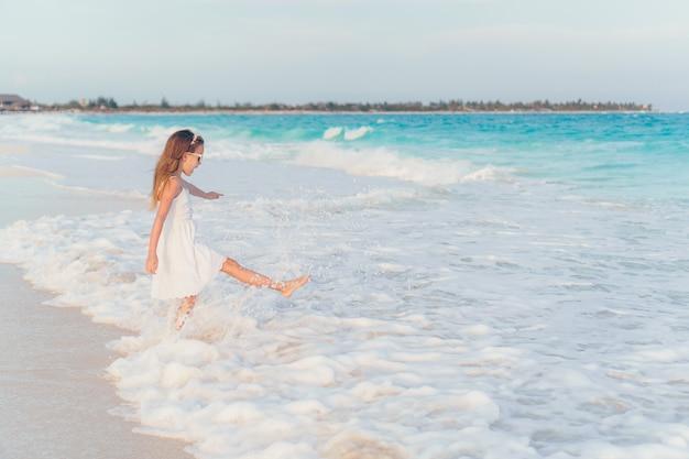 Очаровательны маленькая девочка на пляже, весело на мелководье