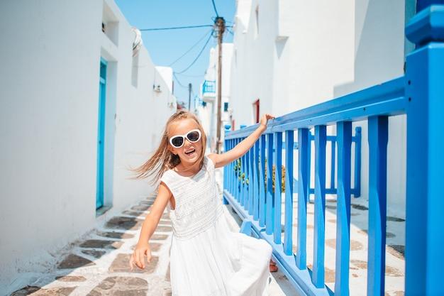 Очаровательная маленькая девочка на старой улице типичной греческой традиционной деревни на миконосе