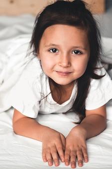 Очаровательная маленькая девочка проснулась в своей постели