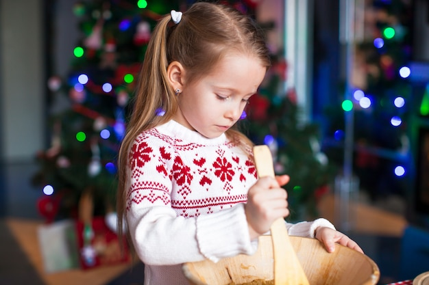Adorable little girl baking gingerbread cookies for christmas at kitchen
