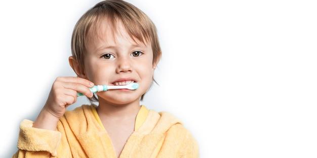 Adorable little girl in bathrobe brushing her teeth