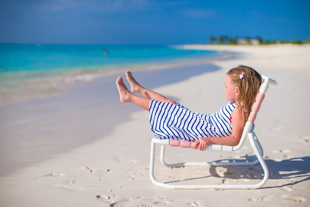 Adorable little girl on beach chair during summer vacation