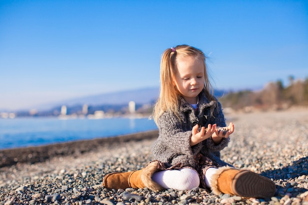 Adorable little girl on the beach in a cozy sweater and dress at warm winter day