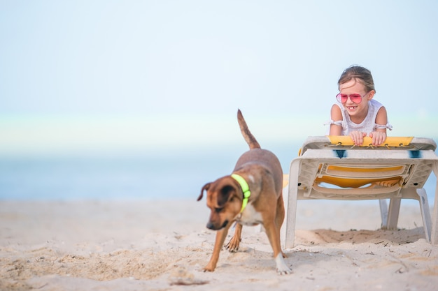 Adorable little girl on the beach playing with dog