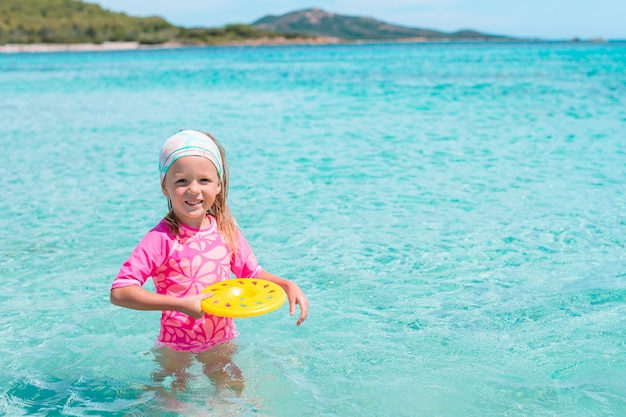 Adorable little girl at beach playing with frisbee