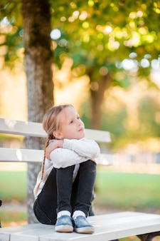 Adorable little girl at beautiful autumn day outdoors. little girl on the bench in fall
