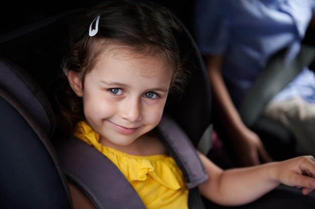窓の外を見て笑っている車の座席にベルトを巻いた愛らしい少女。安全キッズ輸送